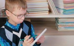 Il ragazzo di sette anni con i vetri disegna qualcosa in uno sketchbook che si siede fra i libri Fotografia Stock