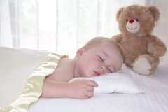 Il ragazzo di un anno sta dormendo sotto la coperta Immagini Stock