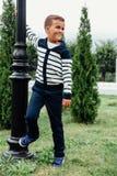 Il ragazzo diligente in saltatore e jeans blu gioca la filatura su una posta della lampada al parco della città Fotografie Stock Libere da Diritti