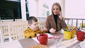 Il ragazzo disegna una madre che parla sul telefono, stock footage