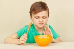 Il ragazzo dispiaciuto poco rifiuta di mangiare il porridge Immagine Stock