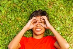 Il ragazzo divertente con le mani sul fronte in vetri modella Fotografie Stock Libere da Diritti