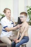 Il ragazzo durante l'esame medico con uno stetoscopio dal pediatra profondamente respira attraverso la bocca aperta immagini stock libere da diritti