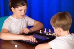Il ragazzo e la ragazza che giocano un gioco da tavolo hanno chiamato Backgammon immagine stock libera da diritti
