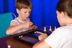 Il ragazzo e la ragazza che giocano un gioco da tavolo hanno chiamato Backgammon immagini stock