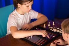 Il ragazzo e la ragazza che giocano un gioco da tavolo hanno chiamato Backgammon immagine stock