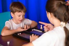 Il ragazzo e la ragazza che giocano un gioco da tavolo hanno chiamato Backgammon fotografia stock