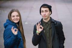 Il ragazzo e la ragazza che mostrano sul fondo bianco passano il segno GIUSTO fotografia stock libera da diritti