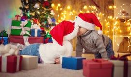 Il ragazzo e la ragazza che si trovano sul pavimento con i presente si avvicinano all'albero di Natale Immagine Stock Libera da Diritti