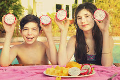 Il ragazzo e la ragazza dell'adolescente dei fratelli germani con il taglio del dracon fruttificano Fotografia Stock