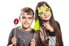Il ragazzo e la ragazza felici, provano sopra le maschere divertenti Fotografia Stock