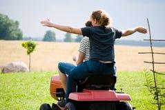 Il ragazzo e la ragazza godono di di guidare un trattore Fotografia Stock