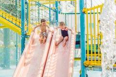 Il ragazzo e la ragazza si divertono nel parco dell'acqua fotografia stock libera da diritti