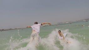 Il ragazzo e la ragazza si imbattono nel mare e cadono in vestiti Fucilazione del movimento lento archivi video