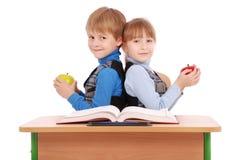 Il ragazzo e la ragazza si siedono ad una mela dello scrittorio e della tenuta della scuola Fotografia Stock