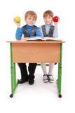 Il ragazzo e la ragazza si siedono ad una mela dello scrittorio e della tenuta della scuola Fotografia Stock Libera da Diritti