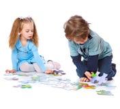 Il ragazzo e la ragazza stanno giocando con il puzzle Fotografia Stock Libera da Diritti