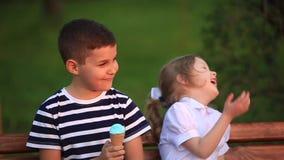 Il ragazzo e la ragazza stanno sedendo sul banco Vada in giro il parco e soffi i denti di leone video d archivio