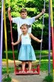 Il ragazzo e la ragazza su un'oscillazione fotografia stock