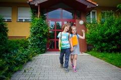 Il ragazzo e la ragazza vanno su un cortile della scuola che si prende per mano Immagine Stock Libera da Diritti