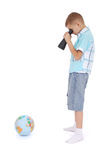 Il ragazzo esamina attraverso il campo-vetro il globo Immagini Stock