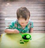 Il ragazzo esamina il suo uovo di Pasqua nella tintura verde Fotografie Stock