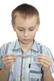 Il ragazzo esamina il termometro. immagine stock libera da diritti
