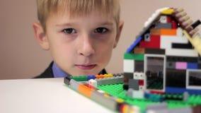 Il ragazzo esamina una casa del giocattolo stock footage