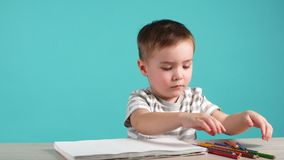 Il ragazzo europeo sveglio disegna la seduta alla tavola con le matite colorate in album archivi video