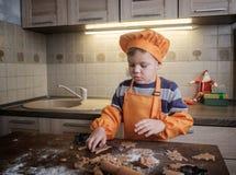 Il ragazzo europeo sveglio in un vestito del cuoco produce i biscotti dello zenzero immagini stock libere da diritti