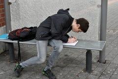 Il ragazzo fa il compito della scuola alla fermata dell'autobus Fotografia Stock Libera da Diritti