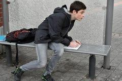Il ragazzo fa il compito della scuola alla fermata dell'autobus Immagine Stock