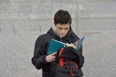 Il ragazzo fa il compito della scuola alla fermata dell'autobus, lui impara i vocables immagini stock