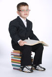 Il ragazzo fa il compito che si siede sulla pila di libri Immagini Stock