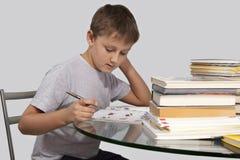 Il ragazzo fa il suo compito con la penna a disposizione nel mezzo giro Immagini Stock Libere da Diritti