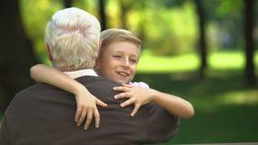 Il ragazzo felice che corre al nonno caro, abbracciante lo, ha assicurato la cura di vecchiaia video d archivio