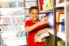 Il ragazzo felice con la mano sullo scaffale per libri tiene molti libri Fotografie Stock
