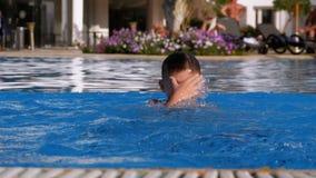 Il ragazzo felice con le alette nuota in uno stagno con acqua blu Movimento lento stock footage