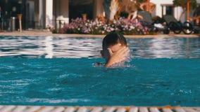 Il ragazzo felice con le alette nuota in uno stagno con acqua blu Movimento lento video d archivio