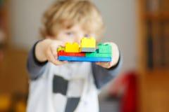 Il ragazzo felice del bambino che gioca con i blocchetti della costruzione con crea Fotografia Stock