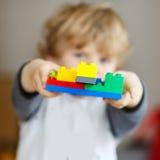 Il ragazzo felice del bambino che gioca con i blocchetti della costruzione con crea Fotografie Stock