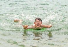 Il ragazzo felice gode di di praticare il surfing nelle onde immagini stock