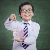 Il ragazzo felice mette la moneta in un porcellino salvadanaio Fotografie Stock Libere da Diritti