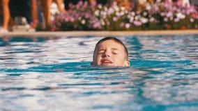 Il ragazzo felice nuota in uno stagno con acqua blu all'hotel Movimento lento stock footage