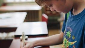 Il ragazzo firma un documento nella biblioteca affitta la post-utilizzazione del libro stock footage
