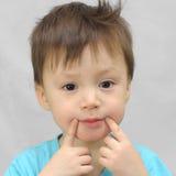 Il ragazzo forza un sorriso Fotografia Stock