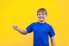 Il ragazzo freckled di felicità che tiene l'oggetto immaginario, esaminante è venuto immagine stock libera da diritti