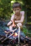 Il ragazzo frigge le salsiccie su un fuoco Il ragazzo nella foresta fotografia stock