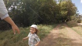 Il ragazzo funziona a sua madre lungo il percorso nel movimento lento della foresta archivi video