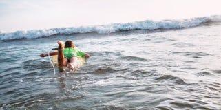 Il ragazzo galleggia sul bordo di spuma verso le onde Immagine Stock Libera da Diritti